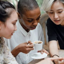 Diverse group of friends checking social media on mobile phone in cafe
